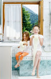 Two sisters playing with toilet paper roll Royalty Free Stock Photography