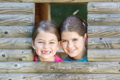 Two sisters playing in tree house Royalty Free Stock Photos