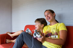 Two Sisters playing video games. Two girls playing video game. One teen one child. White wall and red sofa. Young girl is biting tongue. Elder girl has braces Stock Images