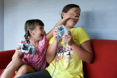 Two Sisters playing video games. Two girls playing video game. One teen one child. White wall and red sofa Stock Photo