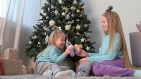 Two sisters playing witn handmade toys and knitted socks near Christmas tree. stock footage