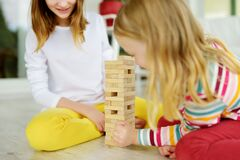 Free Two Sisters Playing Wood Blocks Tower Game At Home. Kids Practicing Their Physical And Mental Skills. Fun Board Games For Family Royalty Free Stock Photo - 176479885