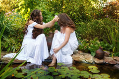 Two sisters at the pond. Two sisters in white dresses at the pond. One girl flower in hair weaves another Royalty Free Stock Image