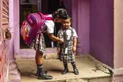 A girl helps her little sister with her school uniform.