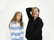 Two sisters posing. Two girls sisters posing one happy one not Royalty Free Stock Photography