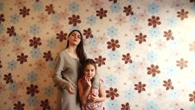Two sisters posing in front of the camera. Against a colorful wall stock video footage