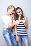 Two sisters posing with mobile phone. Royalty Free Stock Photos