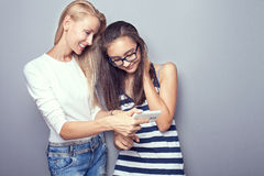Two sisters posing with mobile phone. Two beautiful girls spending time together, watching something on mobile phone. Friends. Studio shot Stock Photos