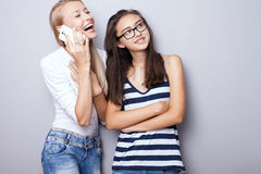 Two sisters posing with mobile phone. Stock Image