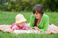 Two sisters reading  book outdoors Royalty Free Stock Image