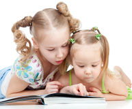Two sisters reading a book together Royalty Free Stock Photo