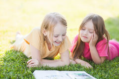 Two sisters reading outdoors, having fun Stock Image