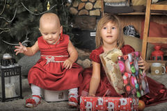 Two sisters in red dresses. Two baby sisters in red dresses with presents Stock Photo