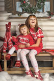 Two sisters in red knitted dresses Royalty Free Stock Image