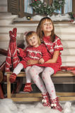 Two sisters in red knitted dresses Royalty Free Stock Photo