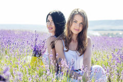 Two sisters are resting on the purple field of lavender Stock Image