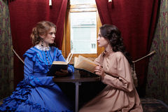 Two sisters in retro dress reading books in train compartment Stock Photography