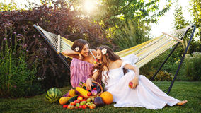Two sisters and rich harvest. Two cute sisters resting after harvesting. Ripe fruits and vegetables. A bountiful harvest. Agriculture Stock Photo