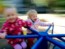 Two sisters riding on a carousel. Two sisters having fun on a carousel. Photo with motion blur Royalty Free Stock Photo