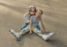 Two sisters roller skating together, wearing protection Royalty Free Stock Images