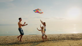Two sisters run for the older brother, who is launching a kite. Happy family and carefree childhood stock footage