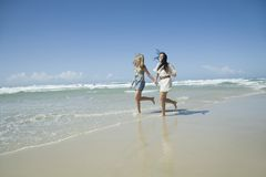 Two sisters running on beach holding hands Royalty Free Stock Photo