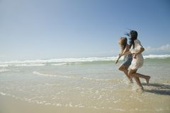 Two sisters running on beach holding hands Stock Photo