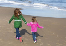 Two sisters running on the beach. Two sisters holding hands while trotting down the beach Royalty Free Stock Photos