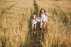 Two sisters running on wheat filed stock photo