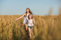 Two sisters running on wheat filed royalty free stock photography