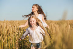 Two sisters running on wheat filed stock image