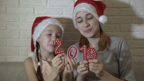 Two sisters in Santa`s hats are holding red numbers 2019 in their hands, playing with them, dancing and smiling sitting. On the couch on a white background stock footage