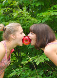 Two sisters sharing an apple. Two sisters sharing an aple in the park on green background of tree leaves Royalty Free Stock Photos