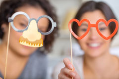Two sisters showing funny party masks Stock Photos