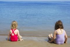 Two sisters sit on beach bathing suit swimsuit Stock Images