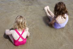 Two sisters sit on beach bathing suit swimsuit stock photography