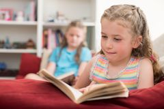 Two Sisters Sitting On Sofa At Home Reading Books Together Stock Image