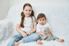 Two children, sisters sit on a white sofa in white t-shirts and blue jeans. Soft plush bear. Two sisters sit on a white sofa in white t-shirts and blue jeans stock photography