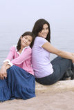 Two sisters sitting by beach Royalty Free Stock Photography