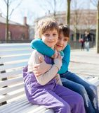 Two sisters sitting on bench in park. Portrait of girlfriends on bench in spring park stock photos