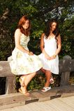 Two sisters sitting on bridge. Royalty Free Stock Photo