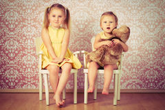 Two sisters sitting on a chair Royalty Free Stock Photography