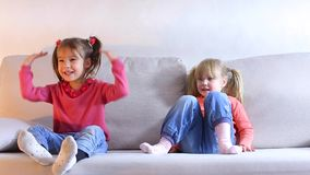 Two sisters sitting on couch, older child playing, little girl offended and angry. Two little sisters sitting on couch in living room, older girl having fun and stock video