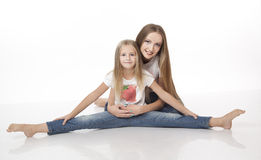 Two sisters sitting on the floor. Gymnastics. Isolated on the wh Stock Photography