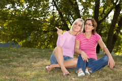 Two sisters sitting in the grass Royalty Free Stock Photo