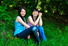 Two sisters sitting on the grass Royalty Free Stock Photos