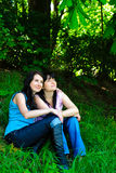 Two sisters sitting on the grass Royalty Free Stock Photo