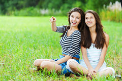 Two sisters sitting grass Royalty Free Stock Photography