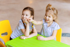 Two sisters sitting at green table Stock Photos