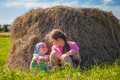 Two sisters sitting at a hay stack Stock Image